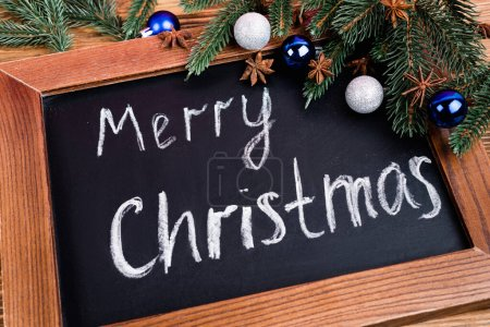 Photo for Close up view of chalkboard with merry christmas lettering near pine branches, baubles and anise stars on brown wooden background - Royalty Free Image