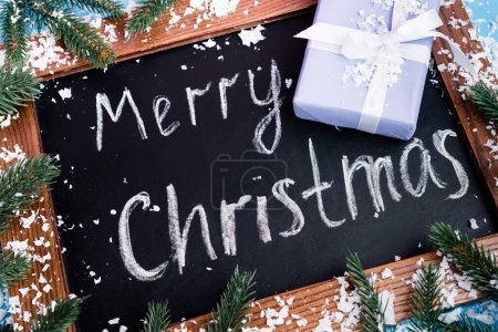 Photo for Close up view of chalkboard with merry christmas lettering near pine branches, little gift box and artificial snow - Royalty Free Image