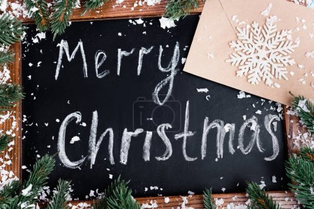 Photo for Top view of chalkboard with merry christmas lettering, pine branches, envelope and decorative snowflake - Royalty Free Image
