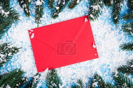 Top view of red envelope, artificial snow and pine branches on blue background, new year concept