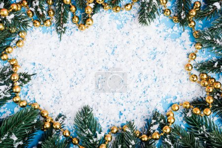 Flat lay with necklace, pine branches and artificial snow on blue background
