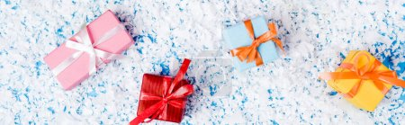 Photo for Top view of little gift boxes with artificial snow on blue background, banner - Royalty Free Image