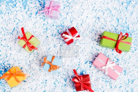 Photo for Top view of little gift boxes with artificial snow on blue background, new year concept - Royalty Free Image