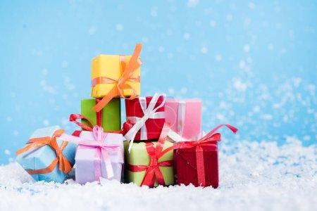Photo pour Niveau de surface des boîtes-cadeaux miniatures avec neige artificielle sur le bleu, concept de nouvelle année - image libre de droit