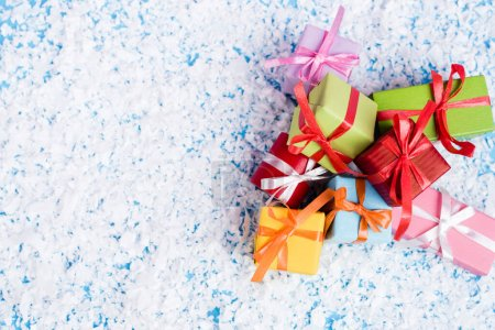 Photo for Top view of little gifts with artificial snow on blue background, new year concept - Royalty Free Image