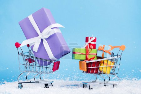 Photo for Surface level of shopping trolleys with little presents on blue background, new year concept - Royalty Free Image