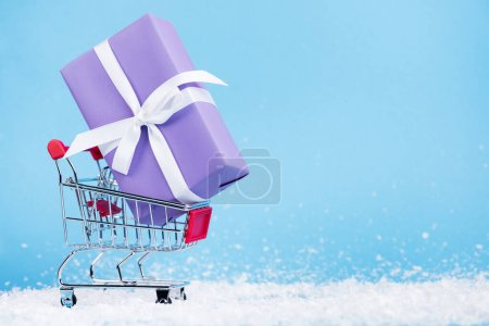 Little gift box in shopping trolley and artificial snow on blue background, new year concept