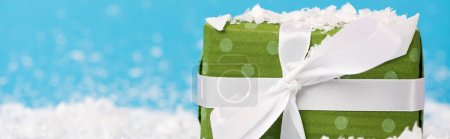 Photo for Close up view of little green gift box with artificial snow on blue background, banner - Royalty Free Image
