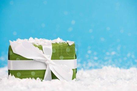 Photo pour Niveau de surface du cadeau miniature avec neige artificielle sur fond flou, concept de nouvelle année - image libre de droit
