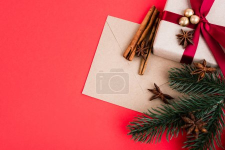 Top view of gift with envelope, cinnamon sticks, anise stars and pine branch on red background