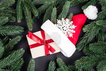 Top view of pine branches, gift box, santa hat and decorative snowflake on black background, new year concept