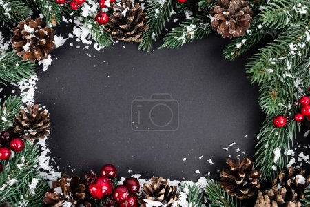 Photo for Flat lay with pine cones, red beads, spruce branches and artificial snow on black background, new year concept - Royalty Free Image