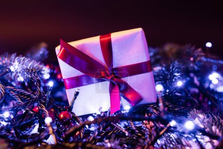 Photo for Surface level of little gift box near pine branches with christmas lights on background, new year concept - Royalty Free Image
