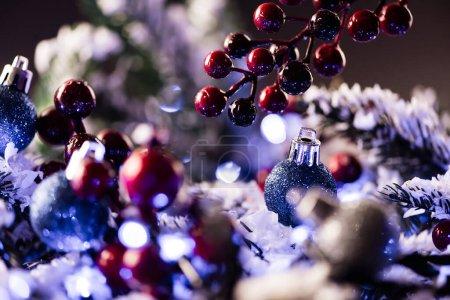 Photo pour Vue rapprochée des perles rouges et des boules avec des branches de pin floues sur le fond, concept de nouvelle année - image libre de droit