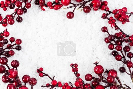 Top view of branches with artificial berries on white textured background, new year concept