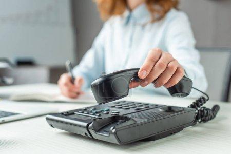 Photo pour Vue recadrée de femme d'affaires mettant combiné sur téléphone fixe sur le lieu de travail sur fond flou - image libre de droit