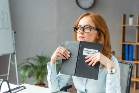 Photo for Thoughtful lawyer holding book with intellectual property lettering, while looking away at workplace on blurred background - Royalty Free Image