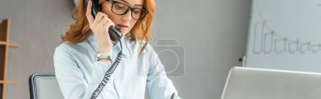 Photo for Redhead businesswoman talking on landline telephone with blurred flipchart on background, banner - Royalty Free Image