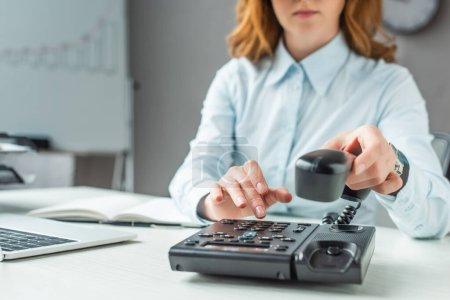 Photo pour Vue recadrée de femme d'affaires avec numéro de téléphone combiné sur téléphone fixe sur le lieu de travail sur fond flou - image libre de droit