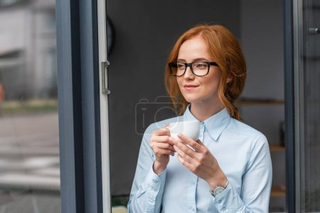 Smiling redhead businesswoman with coffee cup looking away, while standing at window in office