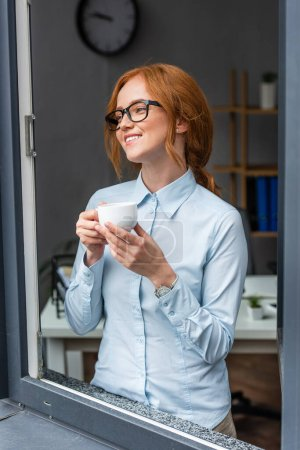 Photo for Happy redhead businesswoman with coffee cup looking away, while standing at window with blurred office on background - Royalty Free Image