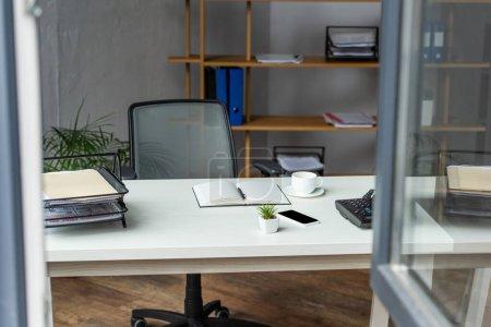 Photo pour Intérieur du bureau avec table, chaise de bureau et étagères avec fenêtre floue au premier plan - image libre de droit