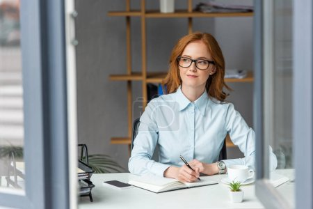 Photo for Positive businesswoman writing in notebook, while looking away at workplace with blurred window on foreground - Royalty Free Image