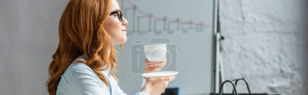 Photo for Side view of redhead businesswoman with coffee cup and saucer looking away with blurred flipchart on background, banner - Royalty Free Image