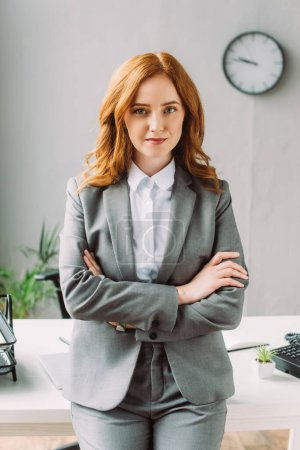 Photo for Front view of positive businesswoman with crossed arms looking at camera, while leaning on table on blurred background - Royalty Free Image
