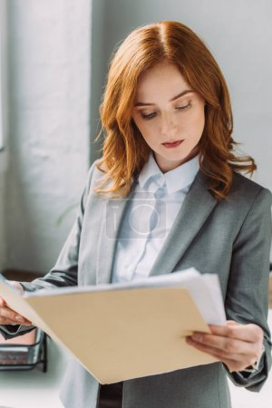 Photo pour Femme d'affaires rousse sérieuse en tenue formelle regardant le dossier avec des documents sur fond flou - image libre de droit
