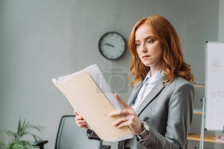 Serious businesswoman looking at folder with documents with blurred office on background