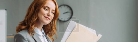 Photo for Positive businesswoman looking at folder with paper sheets with blurred wall clock on background, banner - Royalty Free Image