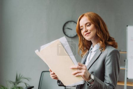 Photo for Smiling businesswoman looking at folder with paper sheets with blurred office on background - Royalty Free Image