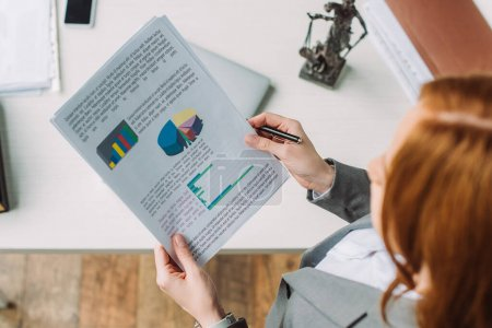 Photo for Overhead view of lawyer holding paper sheets with graphs near workplace with themis figurine on blurred foreground - Royalty Free Image