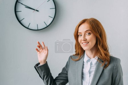 Smiling businesswoman in formal wear pointing with hand at wall clock on grey