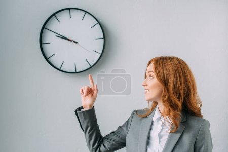 Smiling redhead businesswoman pointing with finger and looking at wall clock on grey