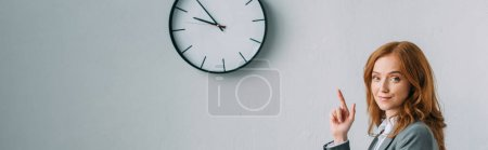 Positive redhead businesswoman pointing with finger at wall clock, while looking at camera on grey, banner