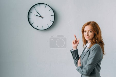 Smiling redhead businesswoman pointing with finger at wall clock, while looking at camera on grey