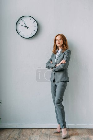 Full length of confident businesswoman with crossed arms standing near wall clock in office