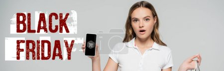 Photo for Shocked woman holding smartphone near black friday lettering and cart illustration on grey, banner - Royalty Free Image