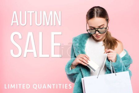 Photo for Trendy woman in sunglasses holding credit card near shopping bag and autumn sale lettering on pink - Royalty Free Image