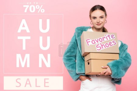 Photo for Pleased woman in sunglasses holding boxes with favorite shoes near autumn sale lettering on pink - Royalty Free Image