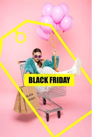 Photo pour Jeune femme en lunettes de soleil assis dans un chariot avec des sacs à provisions et tenant des ballons près de noir vendredi lettrage et étiquette sur rose - image libre de droit