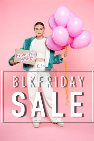 young woman holding carton box with favorite shoes and balloons while standing near blk friday sale lettering on pink