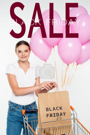 joyful woman holding shopping bag near cart and pink balloons and black friday sale lettering on white