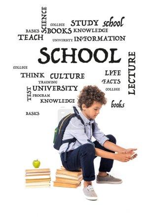 Photo pour Écolier bouclé avec sac à dos assis sur des livres près de pomme et lettrage tout en utilisant smartphone sur blanc - image libre de droit