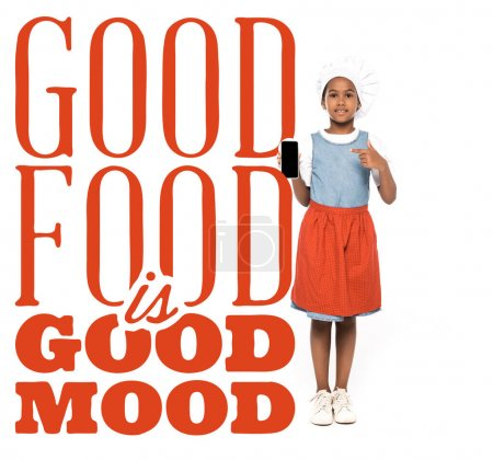 Photo pour Afro-américain enfant habillé en costume de chef pointant du doigt smartphone près de la bonne nourriture est lettrage de bonne humeur sur blanc - image libre de droit