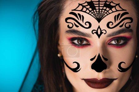 Photo pour Gros plan de la femme avec maquillage noir et illustration sur le visage en regardant la caméra sur bleu - image libre de droit