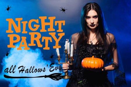 Photo pour Femme pâle avec un maquillage effrayant tenant la citrouille et brûlant des bougies près de la fête de nuit tous les hallows veille lettrage sur bleu avec de la fumée - image libre de droit