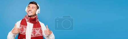 Photo for Happy man with closed eyes, showing thumbs up, while wearing wireless headphones isolated on blue, banner - Royalty Free Image